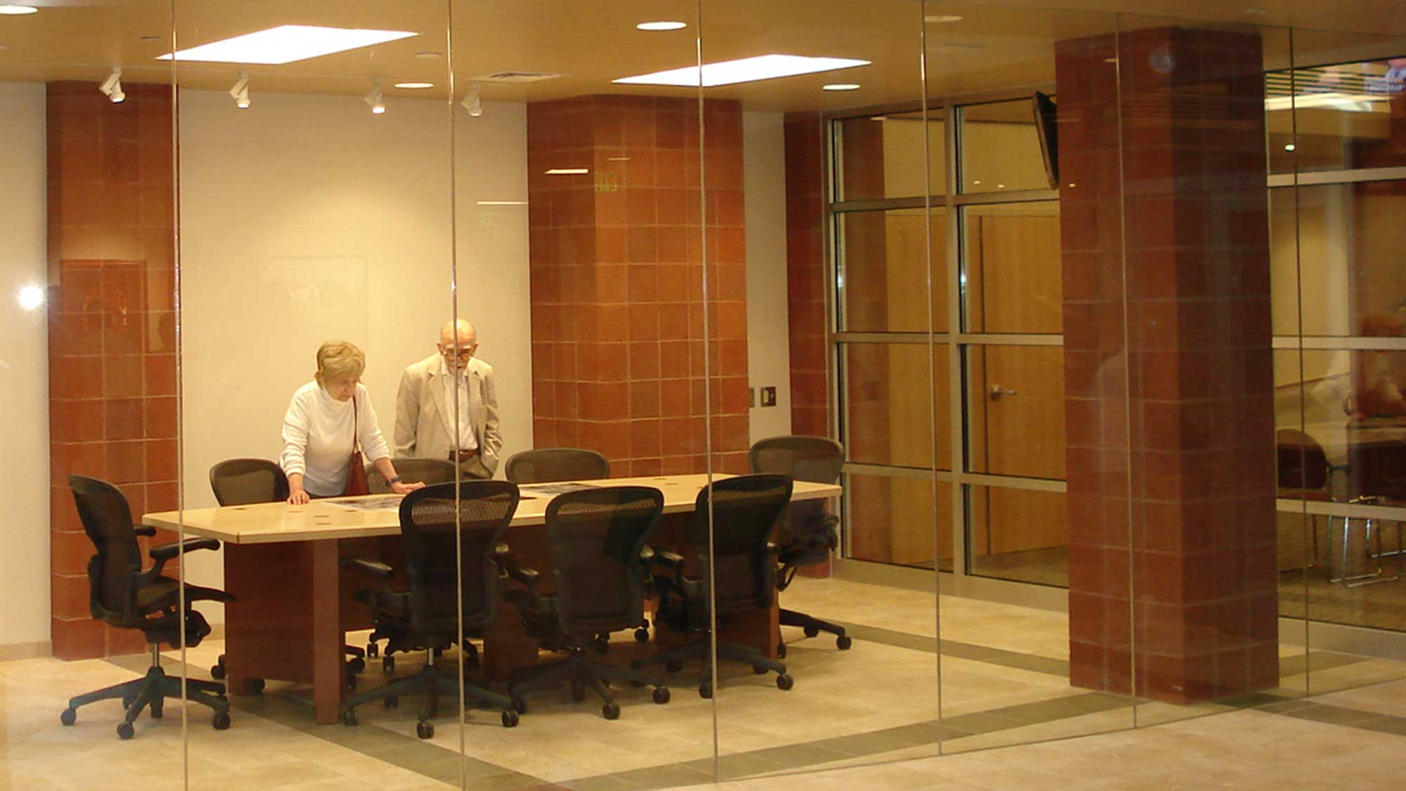 Clients meet at a large table in a room made of glass walls